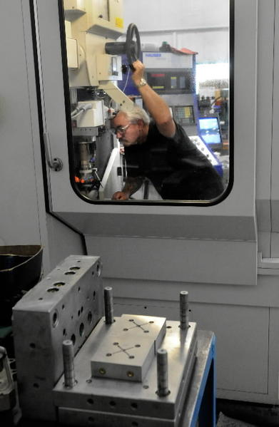 Machinist Colin Saulnier sets up a CNC machine to drill holes in a steel mold cavity at ABA-PGT Inc. in Manchester. The State Bond Commission is expected to approve funds for new machines, including CNCs, for Cheney Technical High School students.