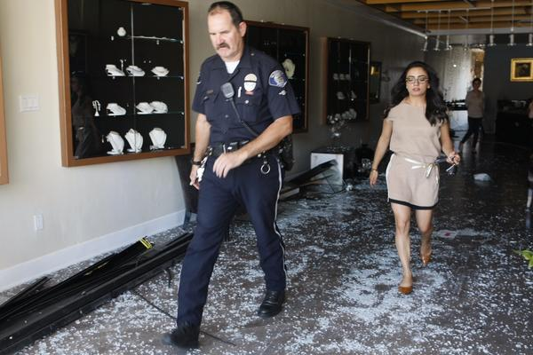 Arka Bijouterie owner Katrine Davtyan walks with a Glendale Police officer in her store after a car plowed into it at 305 N. Brand Blvd. in Glendale on Wednesday, Sept. 25, 2013.