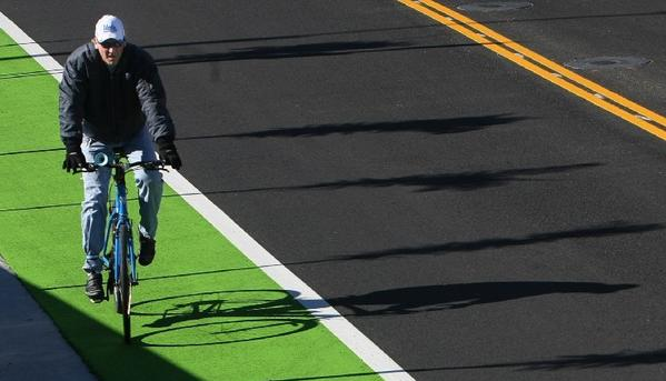 A bicycle rider makes his way along a completed portion of the green bike lane on Ocean Park Boulevard in Santa Monica.