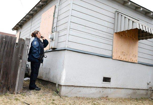 Richmond Police code enforcement officer Lorena Burciaga calls in a utility meter number at a foreclosed home in Richmond, Calif.