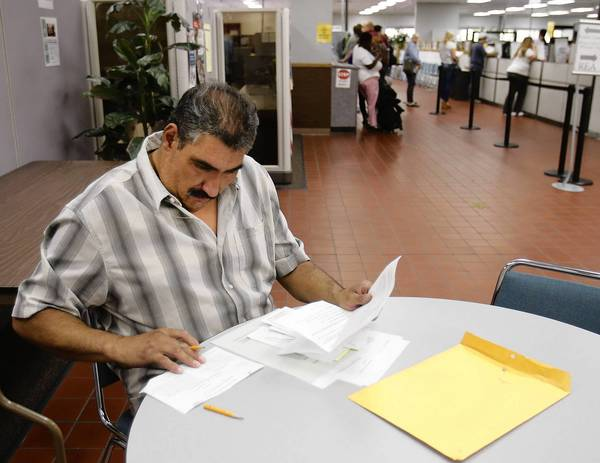 Payments to 124,000 jobless Californians have been delayed by a computer glitch. Above, Luis Rodriguez, who has been out of work, fills out forms at the California Employment Development Department office in Sacramento.