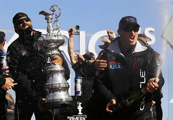 Skipper James Spithill (R) sprays champagne with members of the Oracle Team USA after winning the 34th America's Cup.