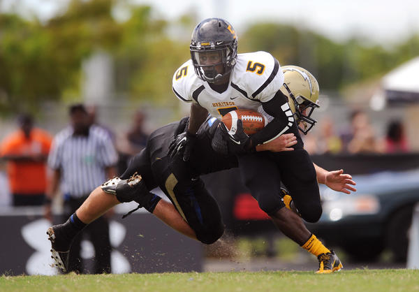 American Heritage's Isaiah McKenzie eludes the tackle of Cypress Bay's Hunter Brown.