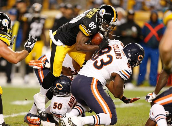 The Steelers' Jerricho Cotchery battles for extra yards after a fourth quarter catch over Nate Collins.