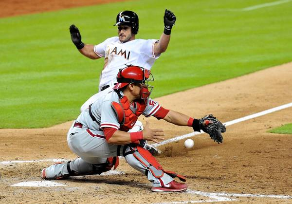 Sep 25, 2013; Miami, FL, USA; Miami Marlins center fielder Justin Ruggiano (20) slides home safely past Philadelphia Phillies catcher Carlos Ruiz (51) during the eighth inning at Marlins Park.