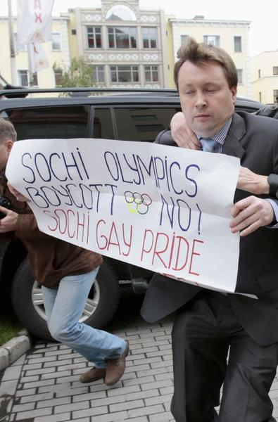 An unidentified man detains gay rights activist Nikolai Alexeyev in Moscow during a protest against a ban on staging a gay pride parade during the Sochi 2014 Winter Olympic Games. The protest was held in front of the Sochi 2014 organizing committee building, September 25, 2013.