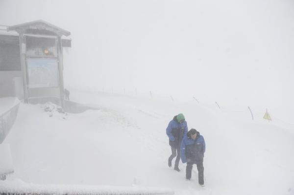 Workers brave strong wind and snowfall in Sochi.