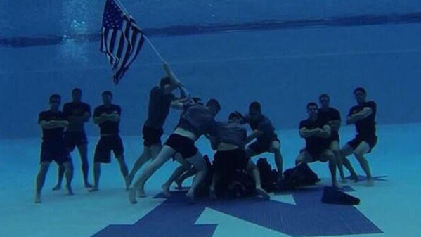 The Navy swimming team, at the bottom of their pool, reenacts the Iwo Jima flag planting.