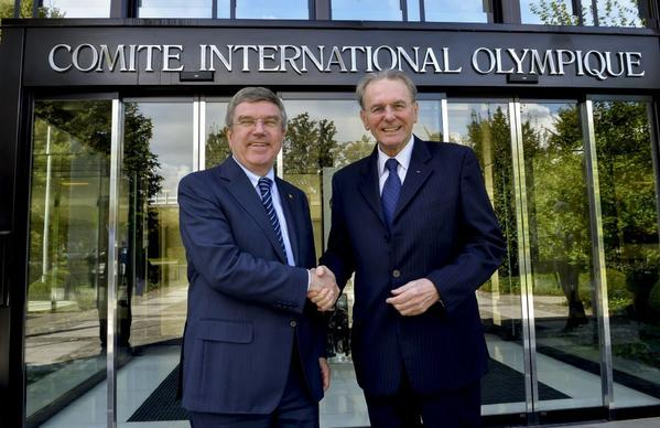 International Olympic Committee President Thomas Bach, left, shakes hands with outgoing IOC President Jacques Rogge in front of the IOC headquarters Sept. 17.