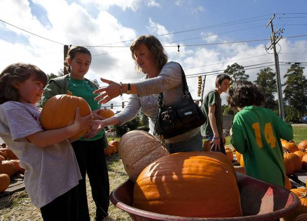 Kaitlin McKeown/Daily Press file photo Sandy Kaiser helps daughters Emily, Megan and Natalie load pumpkins into their cart at the Pumpkin Palooza at Kirkwood Presbyterian Church in Yorktown on Saturday, October 22.