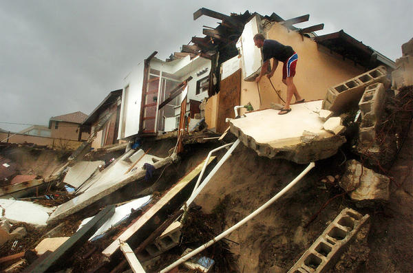 Troy Taynton, of Satellite Beach, Fla, checks the remains of his neighbor's home, Sunday, Sept. 26, 2004.