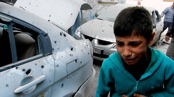 A Syrian boy runs past damaged vehicles during fighting in the Bab Tudmor neighborhood of the restive city of Homs, some 160kms north of the Syrian capital Damascus on February 25, 2012.