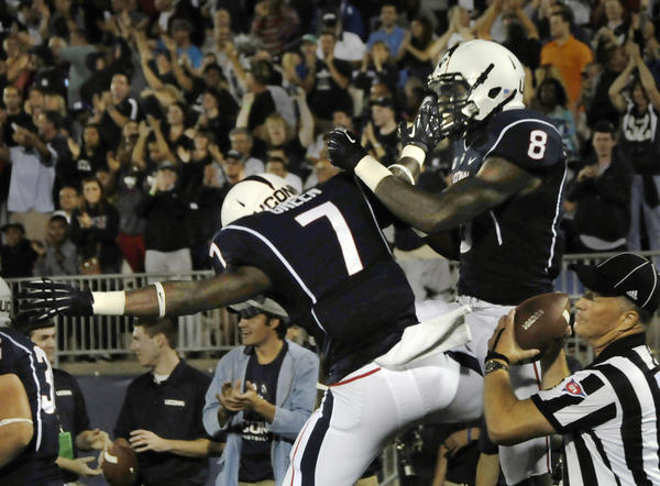 Shakim Phillips celebrates with Jordan Love (7) after scoring UConn's first TD of the season against Towson.