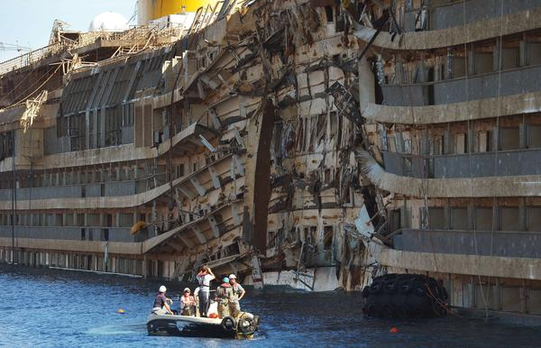 Salvage workers inspect the wreckage of the Costa Concordia cruise ship after it was raised from the water off the Italian coast.