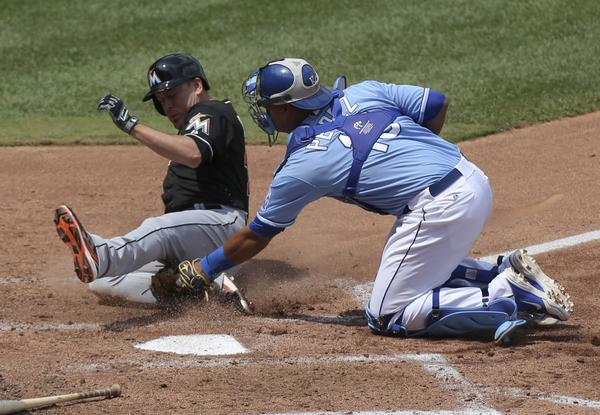 Greg Dobbs #29 of the Miami Marlins is tagged out by Salvador Perez #13 of the Kansas City Royals as he tries to score on a Jake Marisnick single in the fourth inning at Kauffman Stadium August 14, 2013 in Kansas City, Missouri.