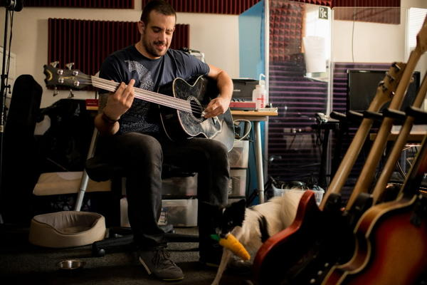 Benn Jordan plays the bass guitar while his dog Lucy walks around his home studio Thursday,