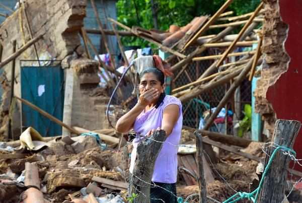 A woman stands amid the rubble of her home at Coyuca de Catalan, in Guerrero state, Mexico on Sept. 24, 2013. The death toll from twin storms that recently lashed Mexico has continued to rise.