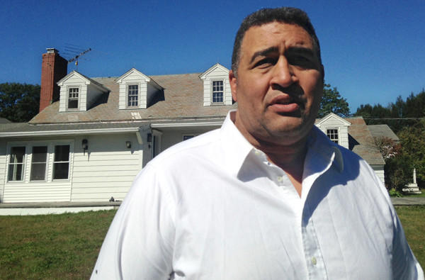Former NFL offensive lineman Brian Holloway stands in front of his vacation home in Stephentown, N.Y.