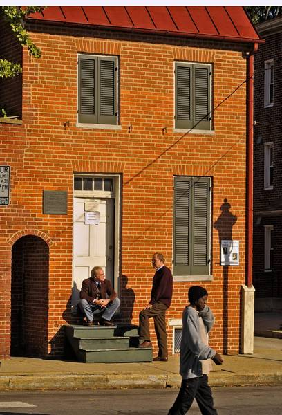In this file photo, Mark Redfield, then the events producer for the Poe House, sits on the steps and chats with Jeff Jerome, then curator, outside Edgar Allan Poe's Baltimore home.