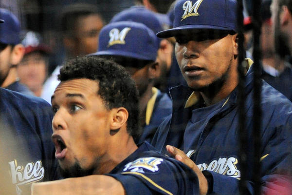 Milwaukee Brewers center fielder Carlos Gomez (27) is restrained by team mates while confronting Atlanta Braves players after hitting a home run during the first inning at Turner Field September 25, 2013.