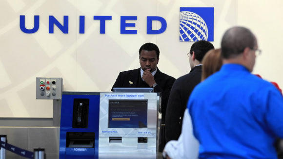 A United employee helps passengers at O'Hare International Airport in November.