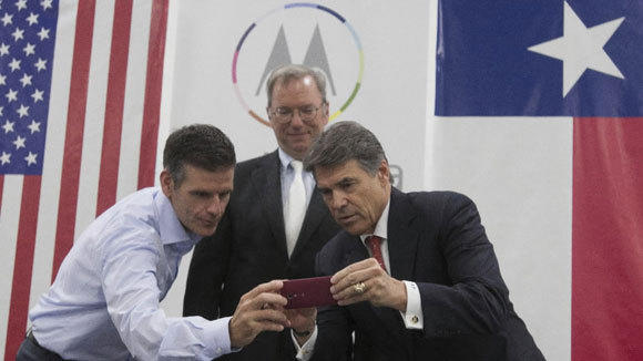 Dennis Woodside, left, chief executive of Motorola Mobility, shows Texas Gov. Rick Perry how to use a Moto X smartphone as Eric Schmidt, executive chairman of Google looks on at a media event in Fort Worth, Texas, where the phones will be manufactured.