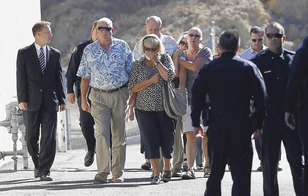 Family members of Laguna Beach officer Jon Coutchie arrive to McCormick & Son mortuary before a motorcade procession on Tuesday.