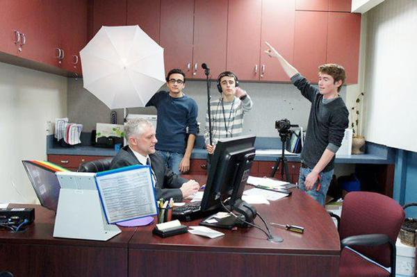 """Hoover High drama teacher Dave Huber sits at a desk during a film project with, from left to right, Artin Aroutounians, Andrew Pirijanian and Reef Oldberg. Aroutounians' film """"Three Degrees"""" was selected for a screening at the AMC Theaters in Times Square."""