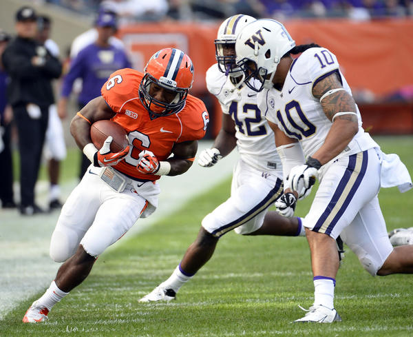 Illini running back Josh Ferguson rushes the ball against Washington's John Timu (10) during the first half at Soldier Field.