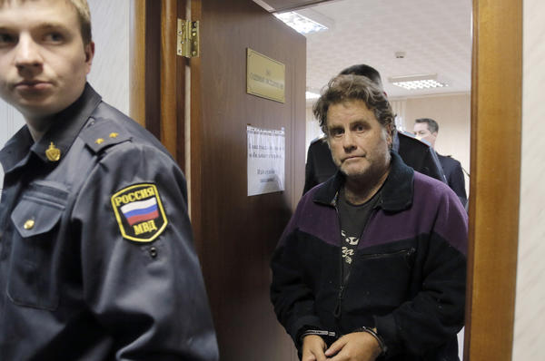 A Russian police officer escorts Greenpeace activist Peter Willcox in court in Murmansk.