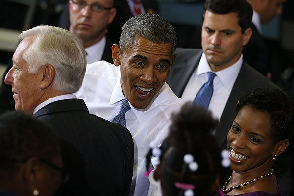 President Obama greets a child flanked by Rep. Donna Edwards (D-Md.), right, and House Majority Whip Steny Hoyer (D-Md.), left, after speaking about healthcare at Prince Georges Community College.