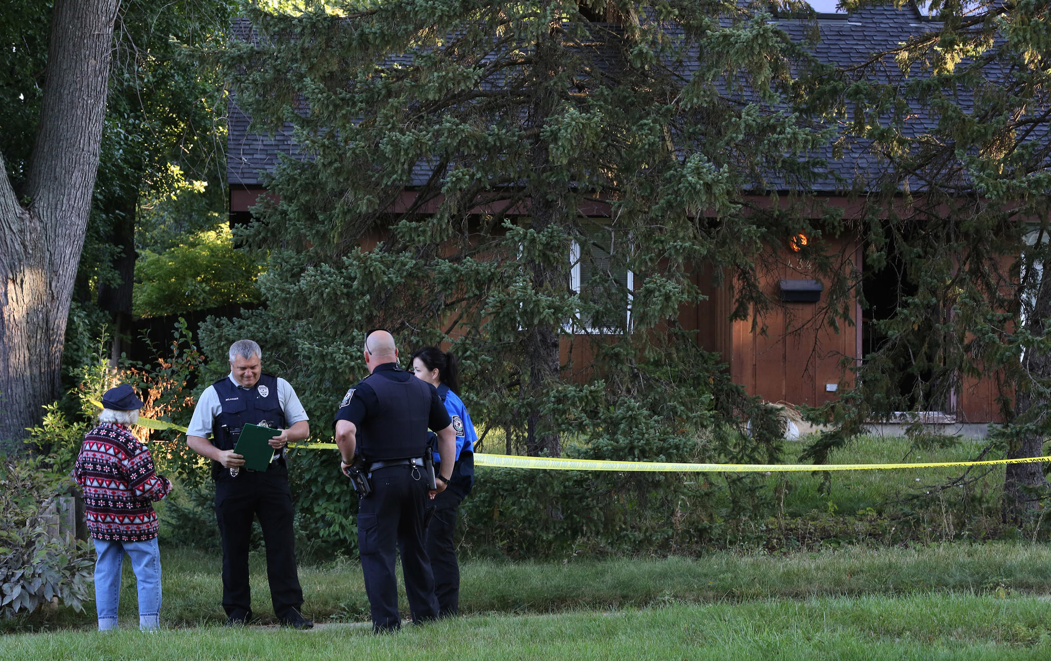 Lombard police speak with a neighbor as they investigate the scene of a shooting in the 400 block of West Harrison in Lombard.