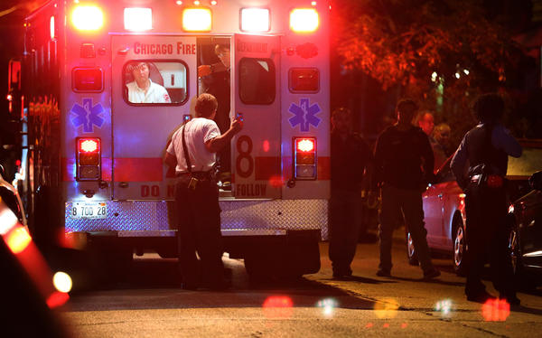 Chicago police board an ambulance where paramedics help a woman shot by a police officer. Police say she pointed a gun toward them in a Pilsen alley. A group of people called 911 after the woman aimed a gun at them in the 1000 block of West Cullerton Street about 10:30 p.m. Thursday, police said.