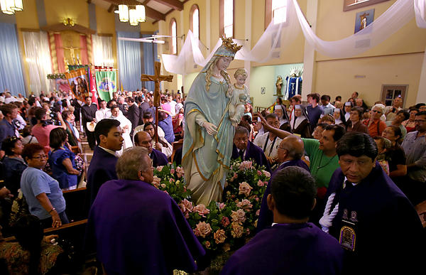 A group of men belonging to the Queen of Angels Foundation carry a statue of the Virgin Mary out of La Placita Church in Los Angeles before parading it through the streets to the Cathedral of Our Lady of the Angels on Sept. 14.