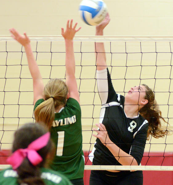 East Jordan junior Katie Spence (right) goes up for an attack against Grayling blocker Courtney Hatfield and during a Lake Michigan Conference match Thursday at the East Jordan High School gym. The Red Devils defeated the Vikings in five sets, 24-26, 15-25, 25-18, 25-23, 15-12.
