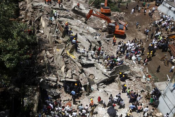 Rescue workers look for survivors and clear debris Friday at the site of a building that collapsed in Mumbai, India.