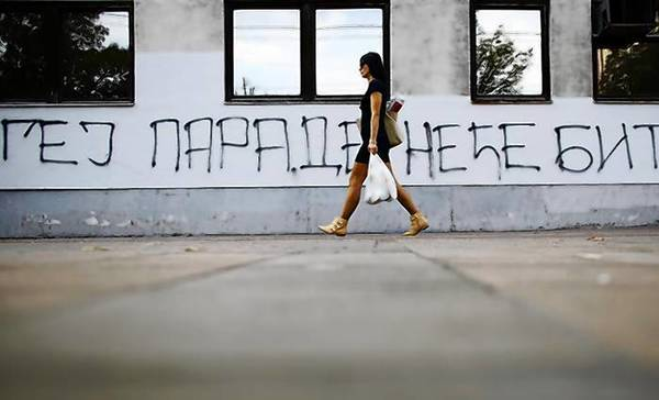 "A woman walks past a graffiti reading, ""Gay parade won't happen"" in Belgrade."