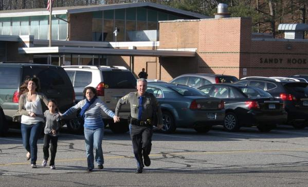 People flee from the Sandy Hook Elementary School in Newtown, Conn., during the shooting rampage by Adam Lanza in December 2012.