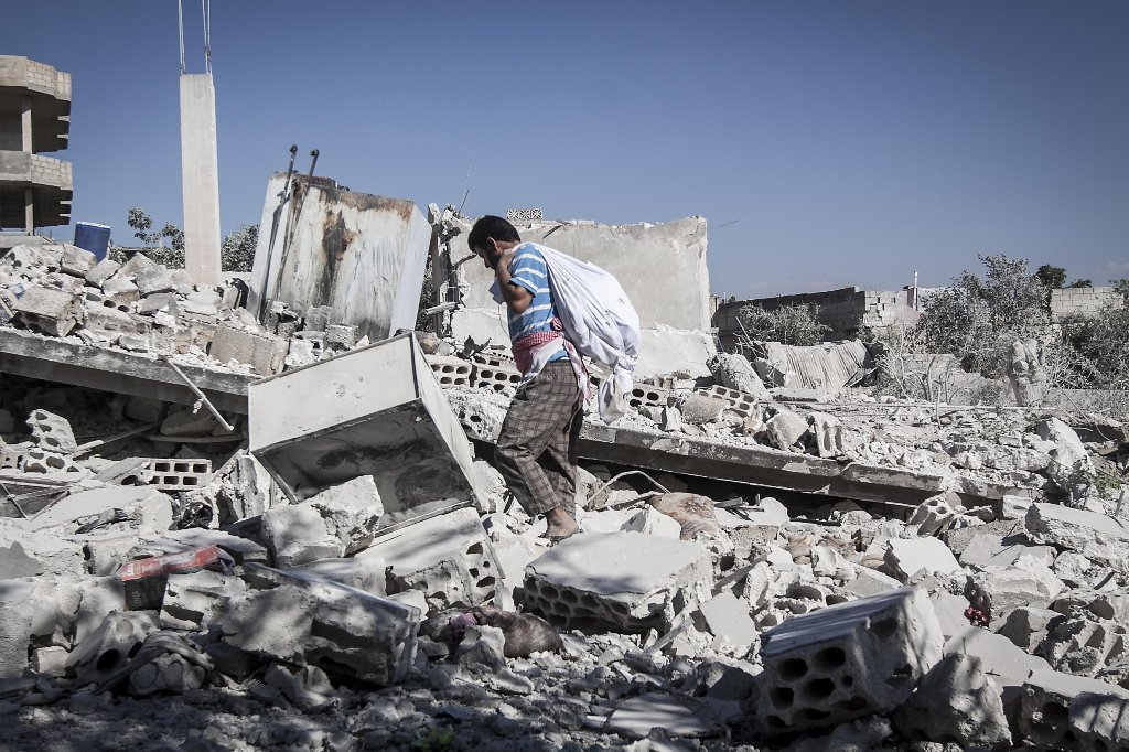 A Syrian man walks among rubble of destroyed residential buildings minutes after an airstrike hit Habit village, in the Syrian central province of Hama, on Wednesday.