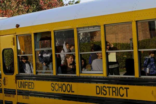 Students are reflected in the windows of an L.A. Unified school bus as they leave the Sherman Oaks Center for Enriched Studies. Shorter school days can be difficult for parents who cannot leave work until hours after their children get out of class.