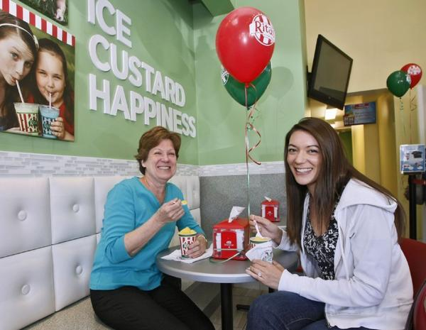 Judy Cosgrove of La Canada Flintridge, left, and her soon-to-be daughter-in-law Megan Dipane, right, enjoy a free regular Italian ice at the grand opening of Rita's.