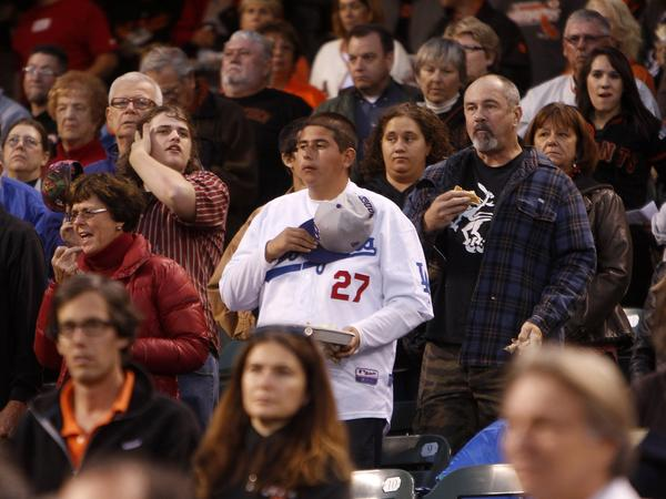 Fans observe a moment of silence before the Giants-Dodgers game Thursday night at AT&T Park for a Dodgers fan who was slain nearby late Wednesday.