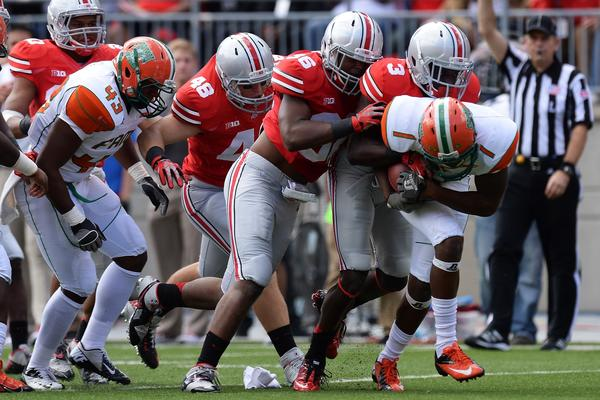 Ohio State's Joe Burger Trey Johnson and Corey Brown gang up to stop the ballcarrier.