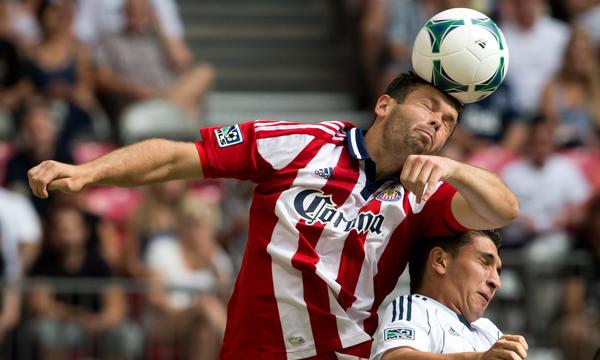 Chivas USA's Bobby Burling, left, heads the ball away from Vancouver's Johnny Leveron during a game earlier this month.