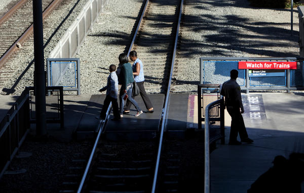 Pedestrians cross the tracks at a Metro Blue Line station. A man was struck and killed Friday evening by a Blue Line train in South L.A., disrupting service during rush hour and causing delays.