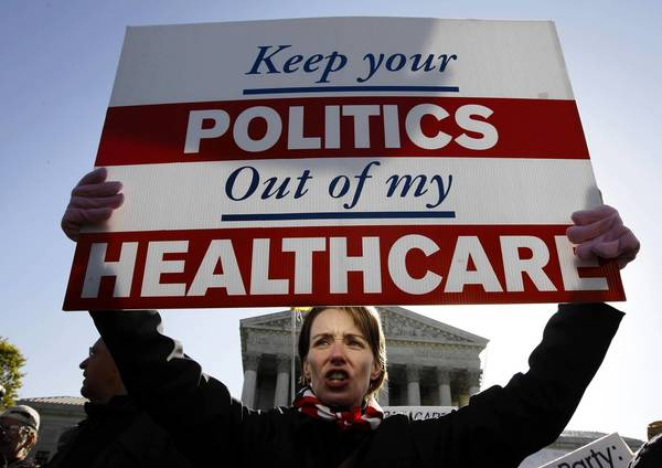 Seen here in March 2012, a protester who opposes President Obama's healthcare reform law demonstrates outside the Supreme Court as the justices hear oral arguments on the law. On Tuesday, the first open enrollment period in the state insurance exchanges will begin.