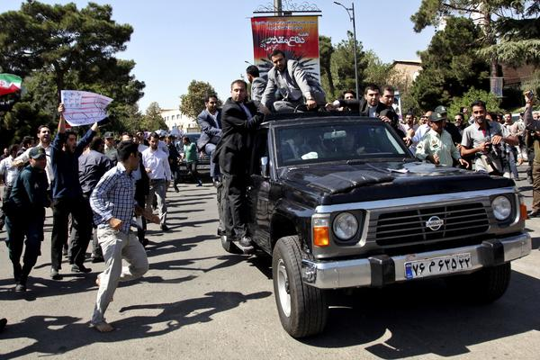 A protester, left, approaches President Hassan Rouhani's car leaving Mehrabad airport after his arrival from the U.S. in Tehran on Saturday.