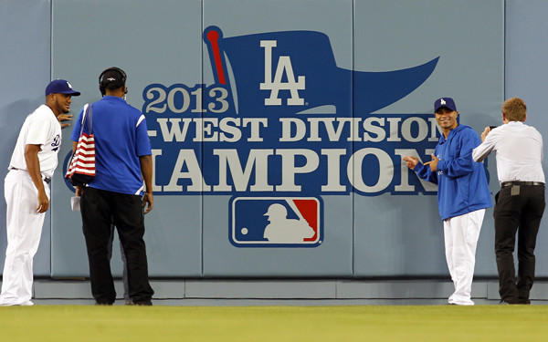 Dodgers pitcher Kenley Jansen, left, and utility player Jerry Hairston at the Dodgers' 2013 NL West Division championship banner before their game against the Colorado Rockies on Friday night.