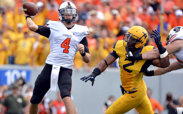 Oklahoma State quarterback J.W. Walsh gets off a pass under pressure from West Virginia linebacker Brandon Golson in the second quarter Saturday.