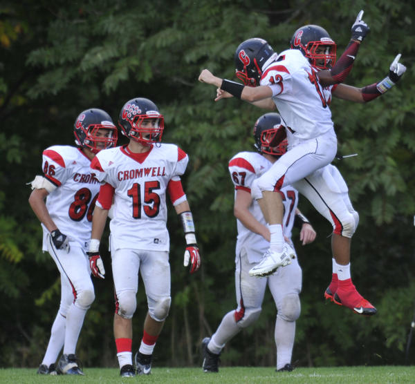 Cromwell's Antwaun Burney, far right, and Mavric Pelletier celebrate a touchdown against Ellington/Somers.